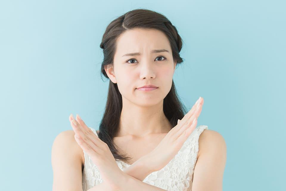 両手で☓をつくる女性