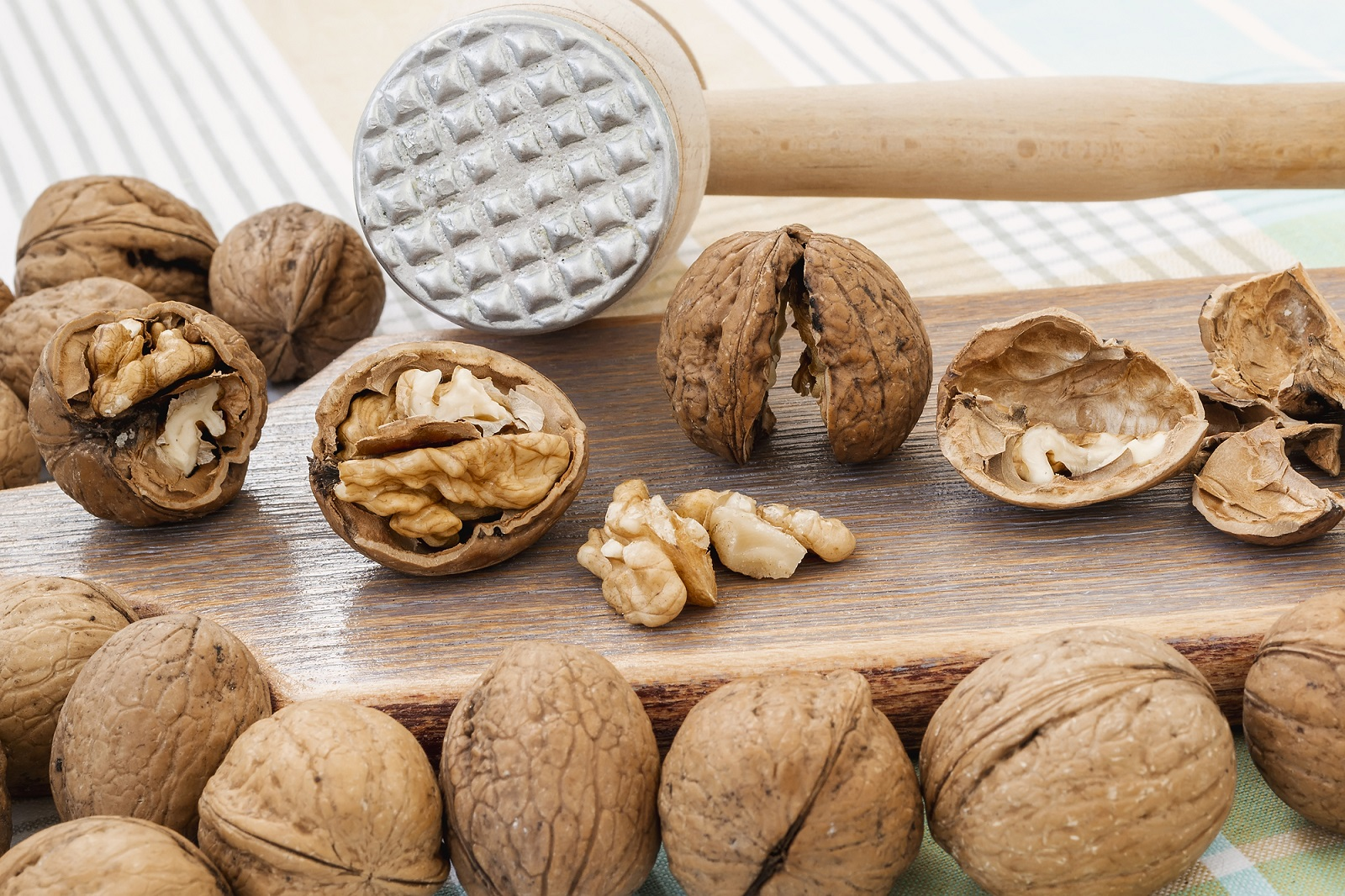 Front view of whole and cracked walnuts (Juglans regia) near wooden meat mallet on a brown wooden board. Natural unbleached nuts. Vegetarian food.