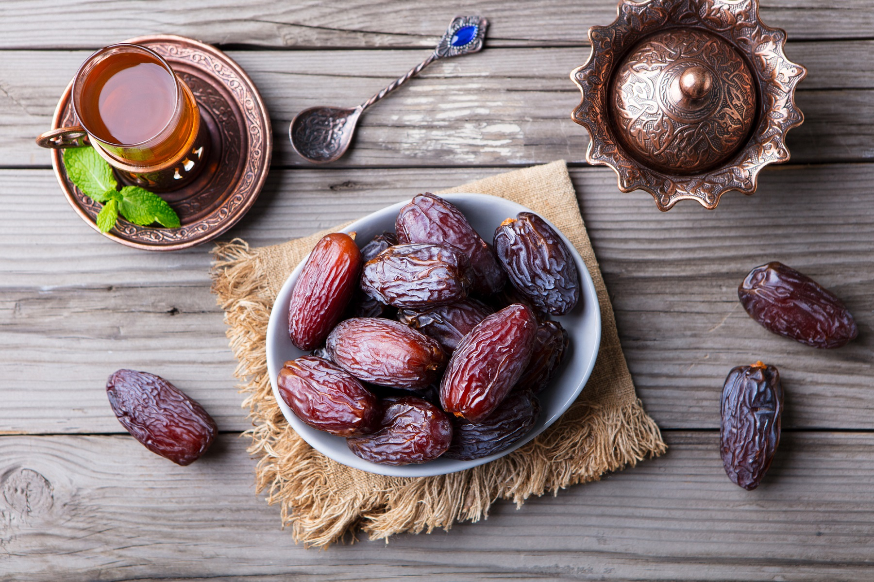 Fresh Medjool Dates in a bowl with tea. Ramadan kareem. Grey wooden background.. Top view