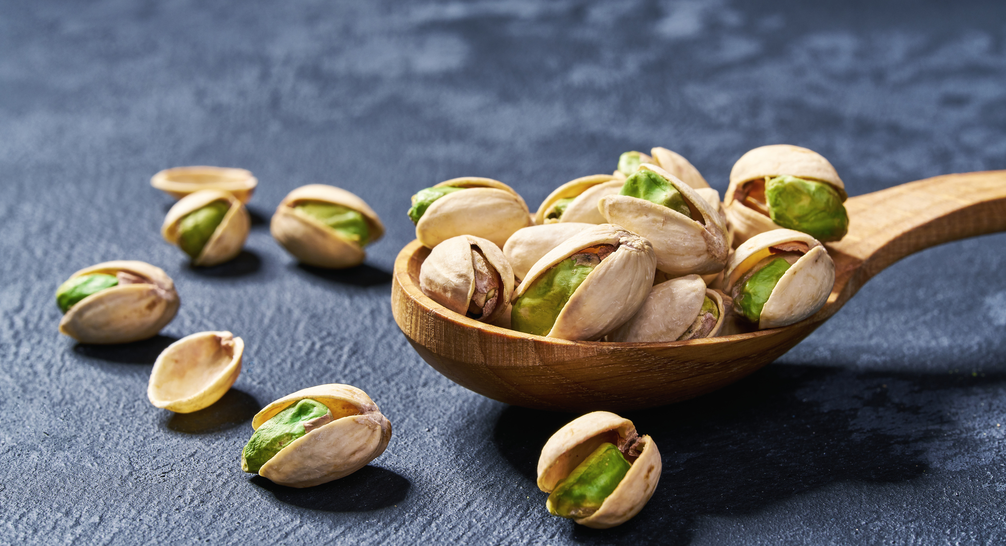 Pistachios in wooden spoon on black table, macro shot.