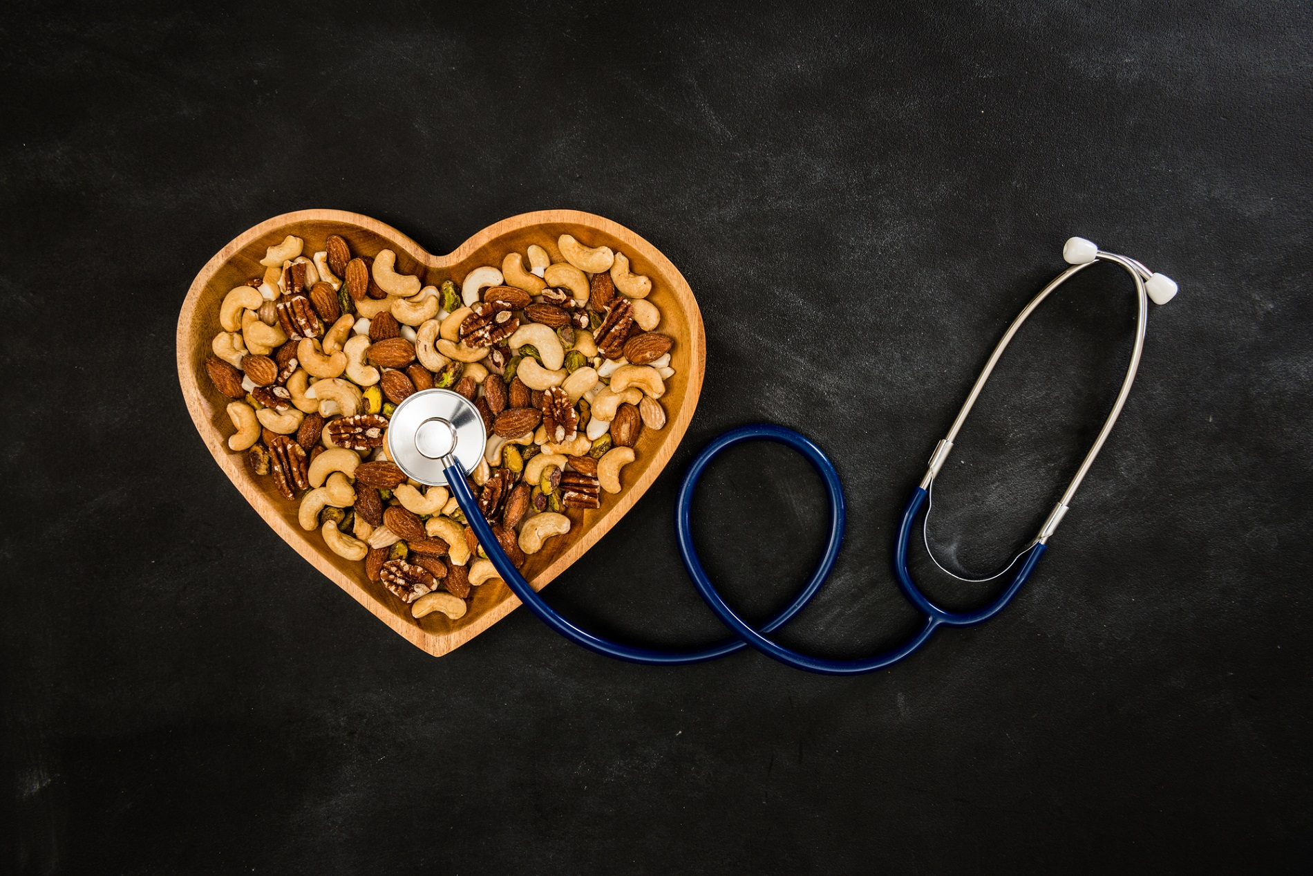 many colorful fresh nuts in love heart shaped wooden vintage plate with stethoscope showing healthcare diet concept on black chalkboard background.